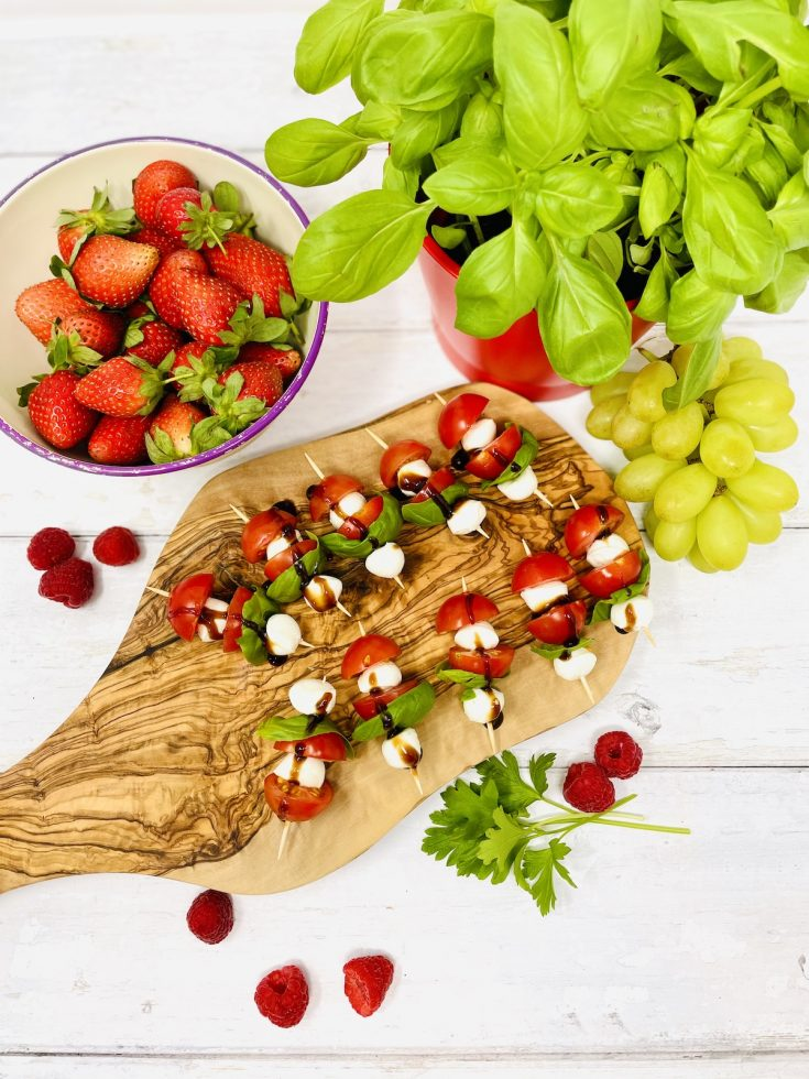 caprese skewers on a wooden graze board surrounded by bowl of strawberries, raspberries, potted basil plant and grapes