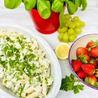 creamy lemon chicken pasta salad scattered with chopped herbs, a bowl of strawberries, bunch of grapes and potted basil plant are by the side of the pasta dish
