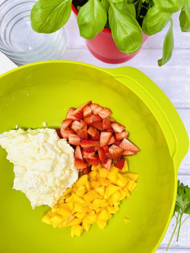 whipped vanilla cream in a bowl with strawberry and mango slices