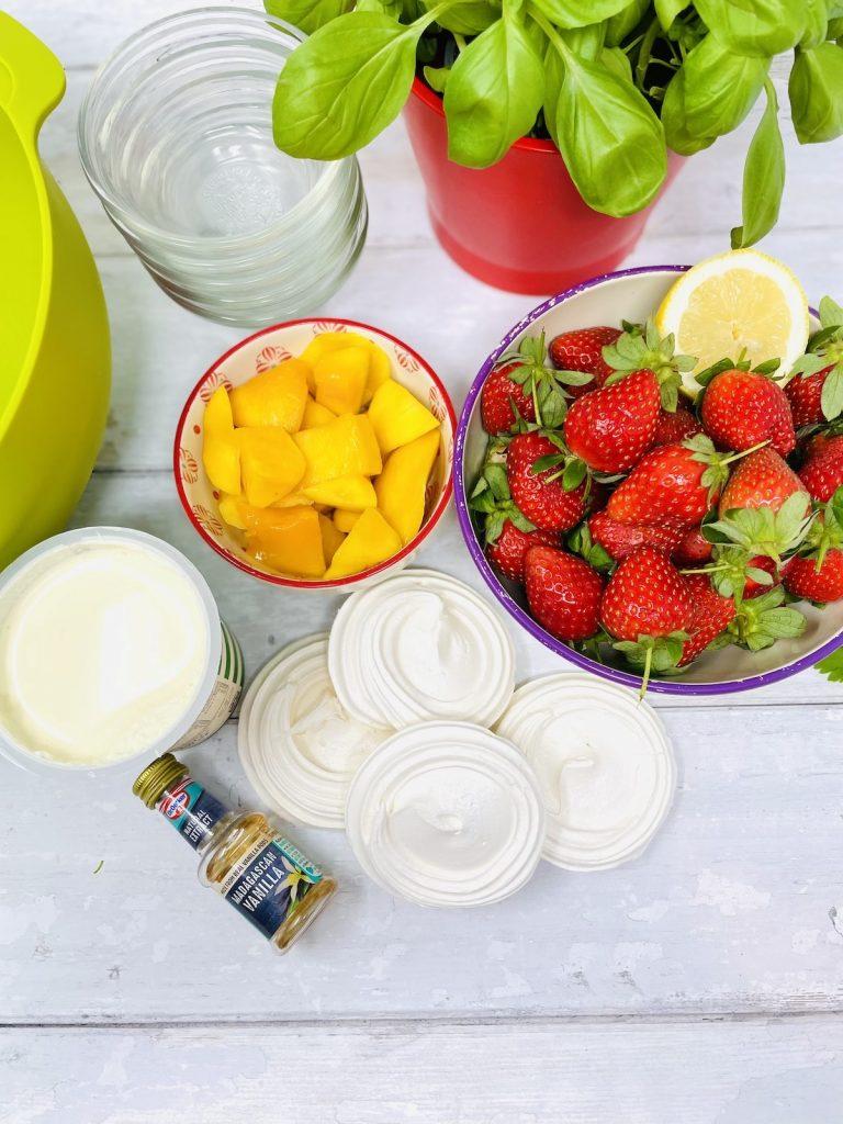 Eton mess ingredients on a white table - strawberries, cream, meringue nests, vanilla extract and mango chunks