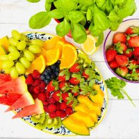 fruit platter with strawberries, melon, grapes, raspberries, oranges and blueberries