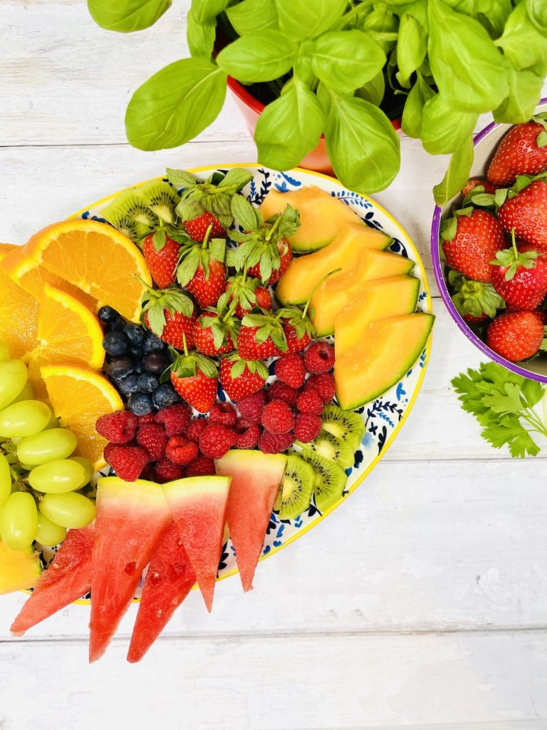 fruit tray with strawberries, melon, grapes, raspberries, oranges and blueberries