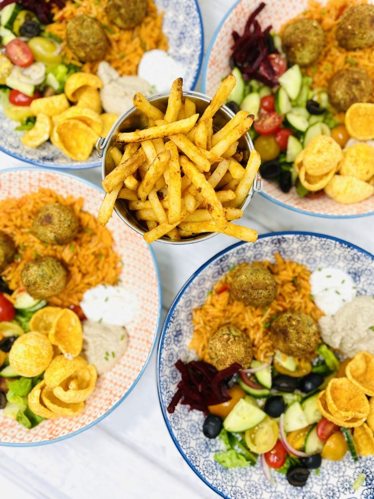 Cauldron foods falafel served with rice and salad and a bucket of fries