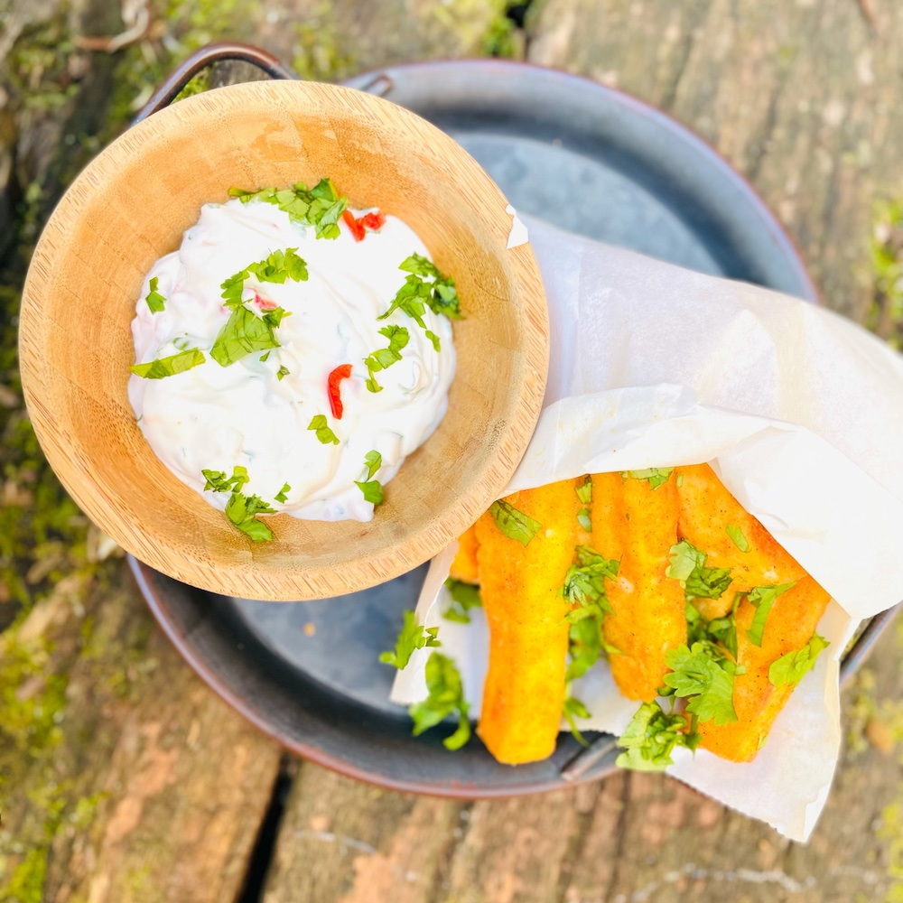 white paper bag filled with homemade halloumi fries scattered with chopped coriander and served with chilli and lemon yogurt dip