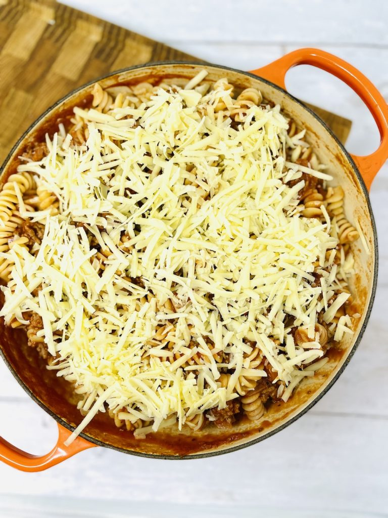 bolognese pasta bake covered in grated cheese ready to bake