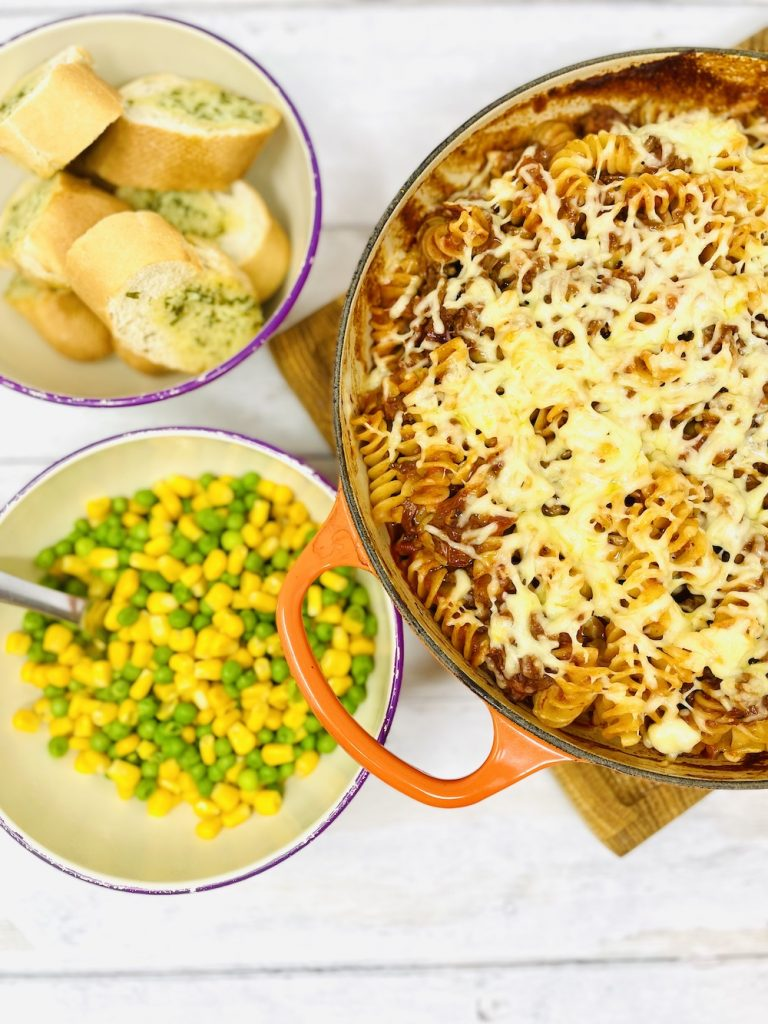 bolognese pasta bake served with peas and sweetcorn and garlic baguette slices