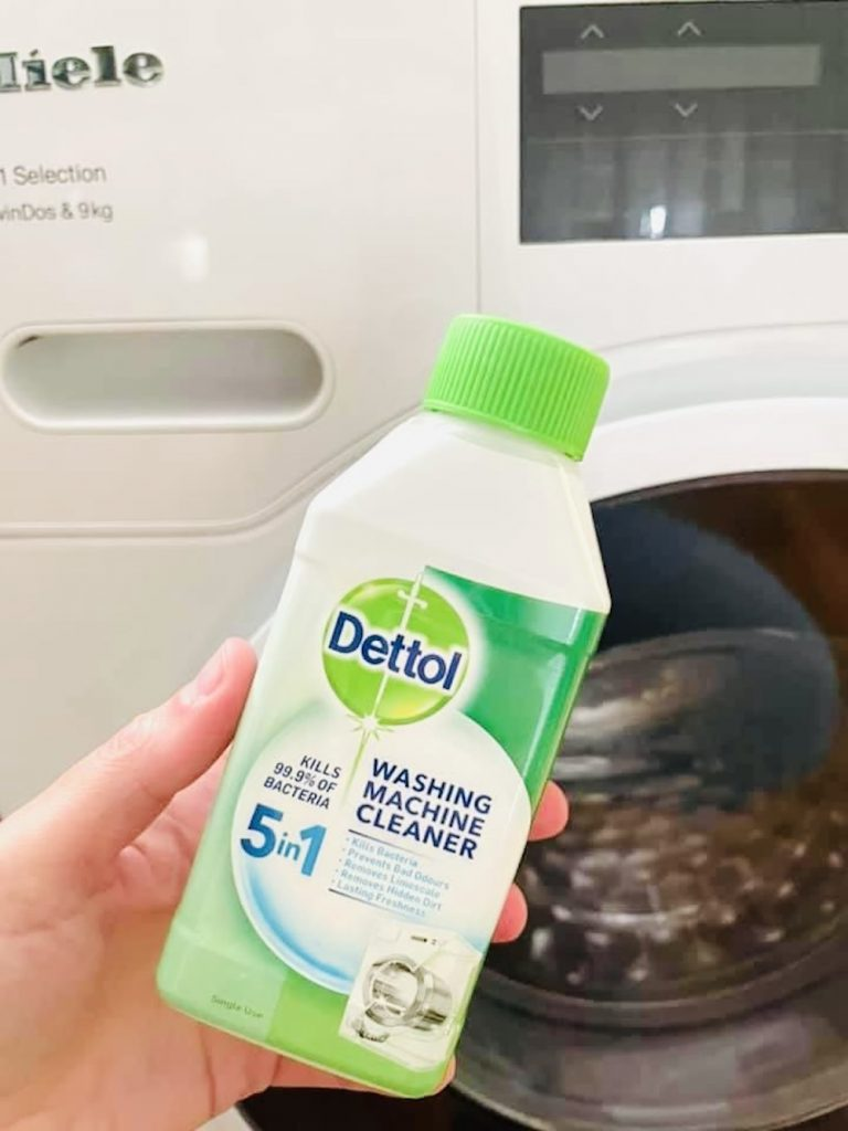 dettol washing machine cleaner being held up in front of Miele washing machine