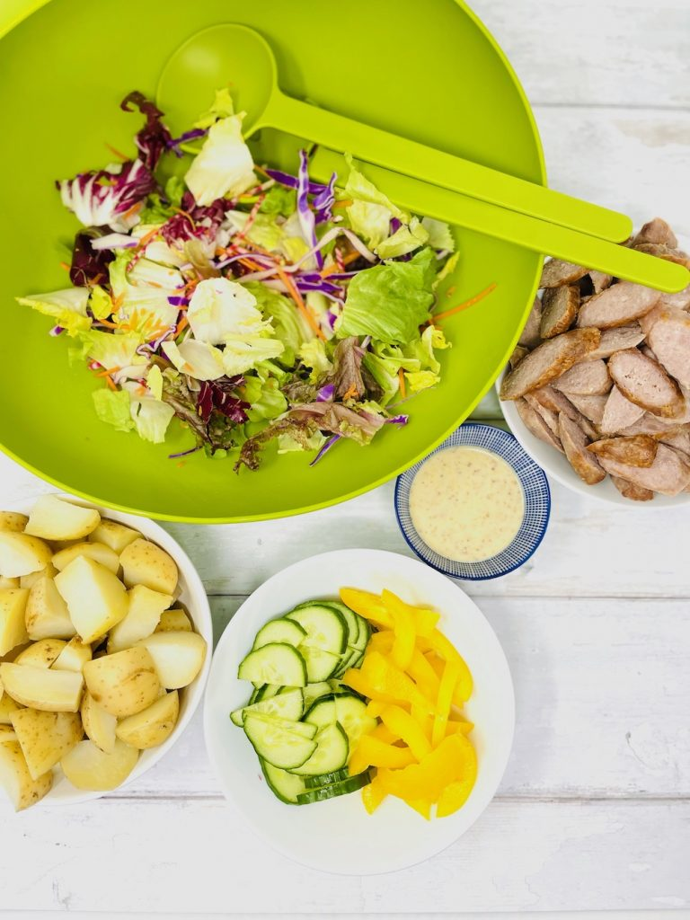 sausage salad ingredients on a table - lettuce leaves, boiled new potatoes, sliced sausages, cucumber slices, pepper slices, honey and mustard dressing