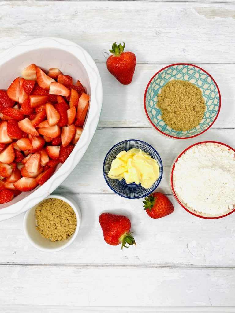 strawberry crumble ingredients - fresh strawberries, brown sugar, plain flour, butter all on a. white table