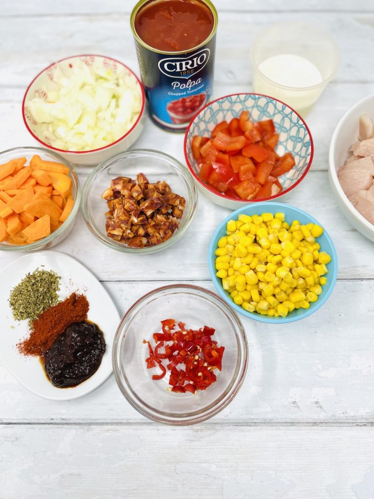 mexican chicken stew ingredients - chicken breast, chorizo, diced onions, carrots, sweetcorn, pepper and red chilli alongside canned tomatoes and spices