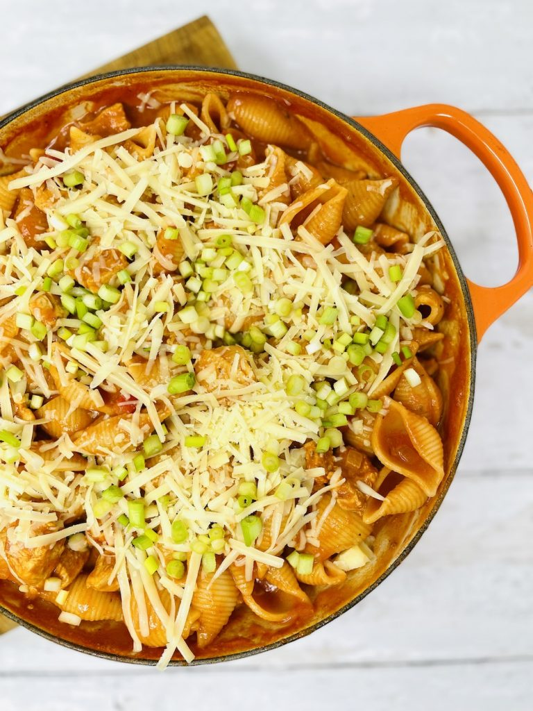 cajun chicken pasta bake topped with grated cheese and spring onions ready to bake in the oven