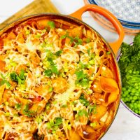 Cajun chicken pasta bake topped with melted cheese and spring onions served alongside a bowl of broccoli and peas