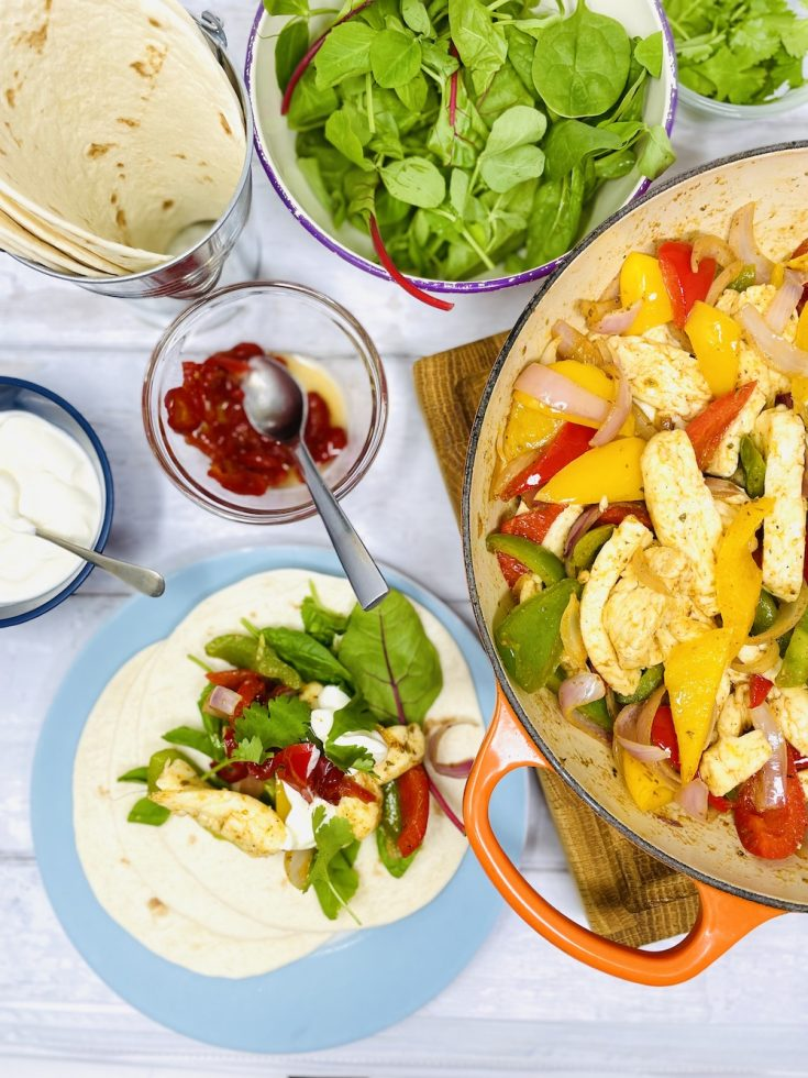 halloumi fajitas with salad, sour cream and candied jalapeños. Panful of halloumi and peppers on the table along with different fajita toppings