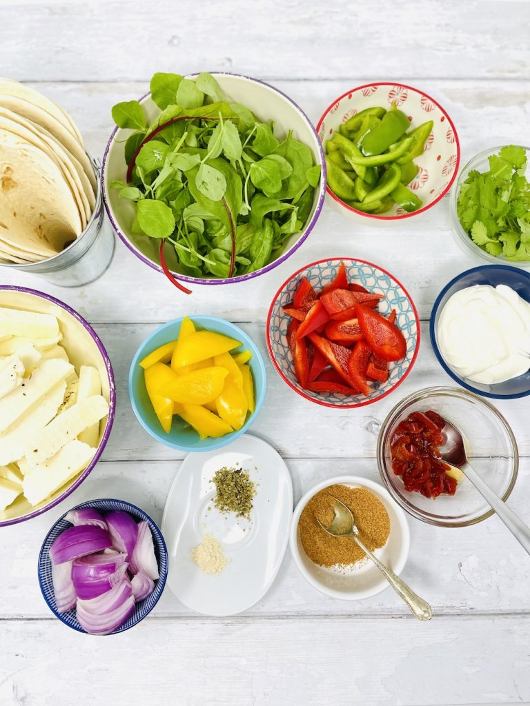 halloumi fajita ingredients on a white wooden table. Halloumi, red, green and yellow peppers, red onion, fajita seasoning, dried oregano, garlic powder, baby leaf lettuce, coriander, soured cream and candied jalapeños