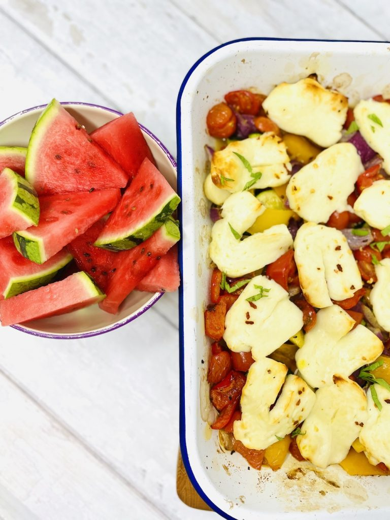 halloumi tray bake served alongside a bowl of watermelon