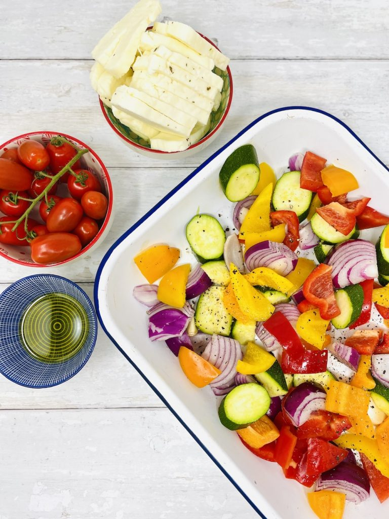 halloumi tray bake ingredients - chopped Mediterranean vegetables, olive oil, baby plum tomatoes and sliced halloumi cheese