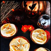 halloween pies with jack o lantern faces on a black slate serving platter