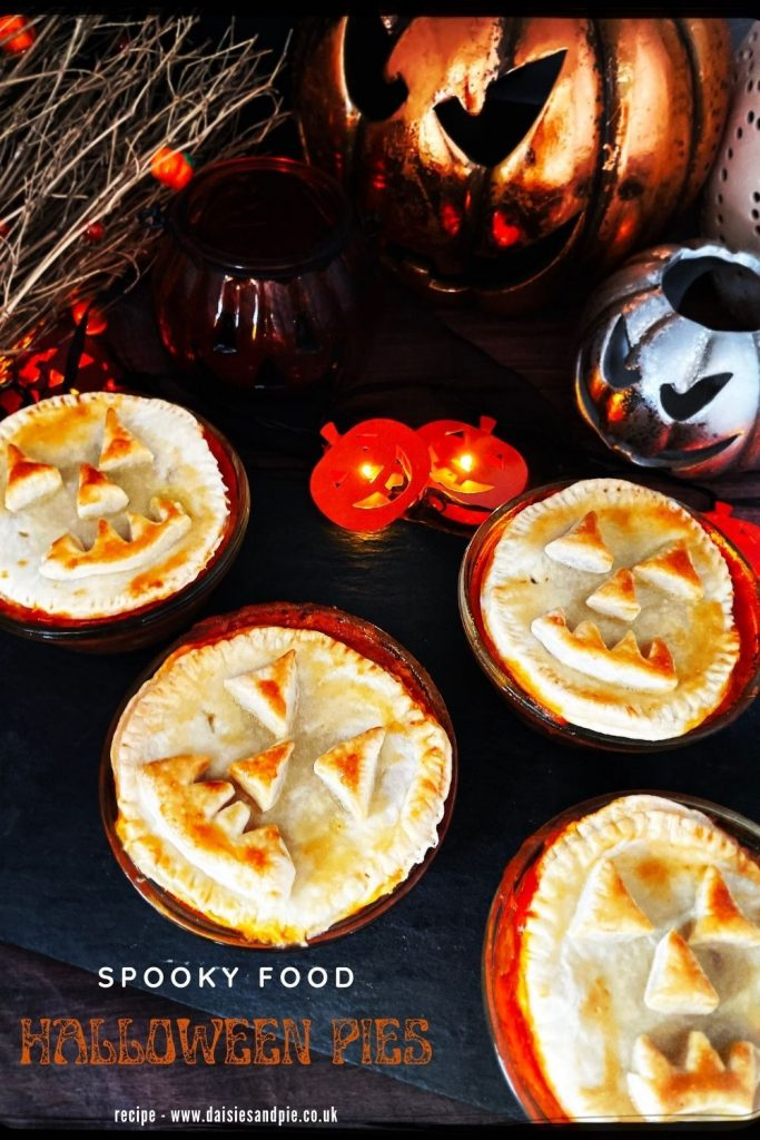 """halloween pies with jack o lantern faces on a black slate serving platter. Text overlay reads """"spooky food - halloween pies"""""""
