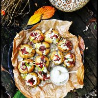 mini baked potatoes stuffed with soured cream dip and topped with bacon sprinkles served on a tray with autumn leaves and pumpkins surrounding