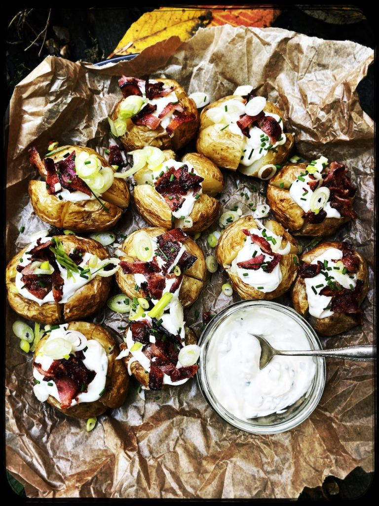 mini jacket potatoes stuffed with soured cream dip and topped with bacon sprinkles served on a tray with autumn leaves and pumpkins surrounding