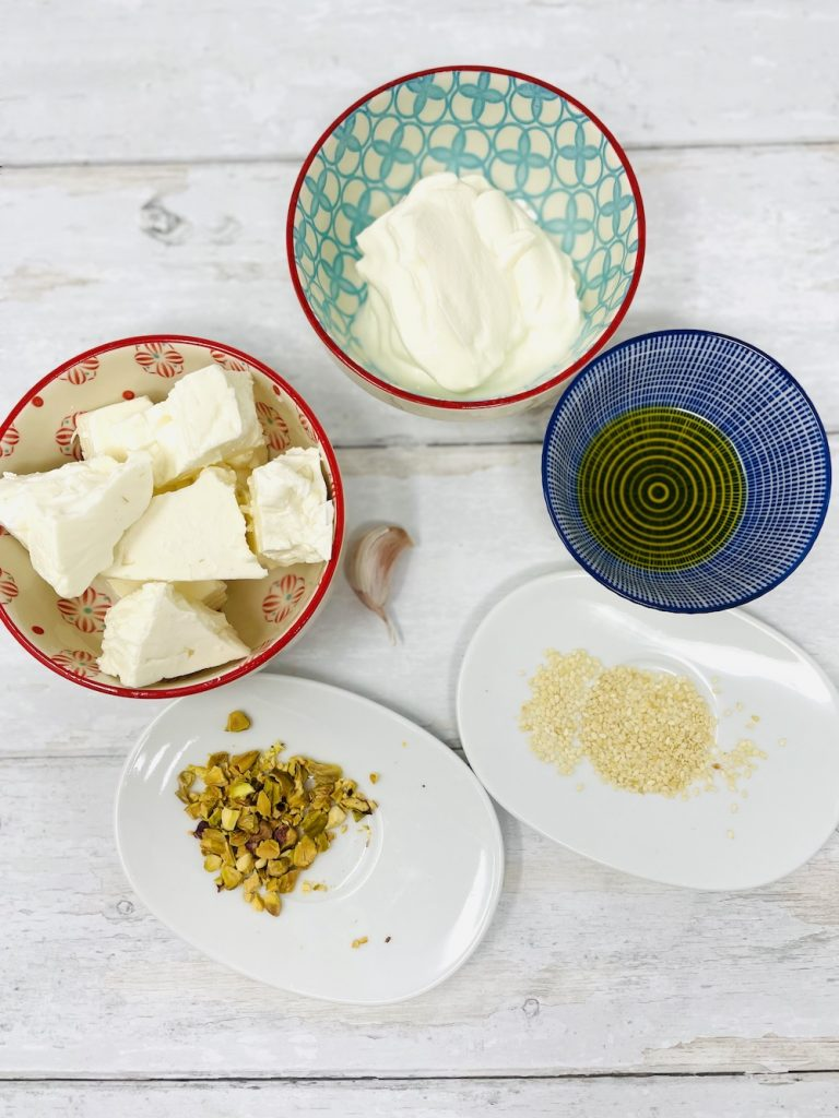 whipped feta ingredients - feta cheese, greek yogurt, olive oil and smashed pistachio nuts and sesame seeds to go on top