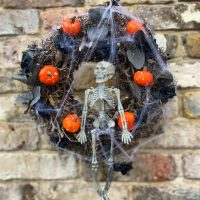 a twiggy Halloween wreath decorated with leaves, mini pumpkins and a skeleton