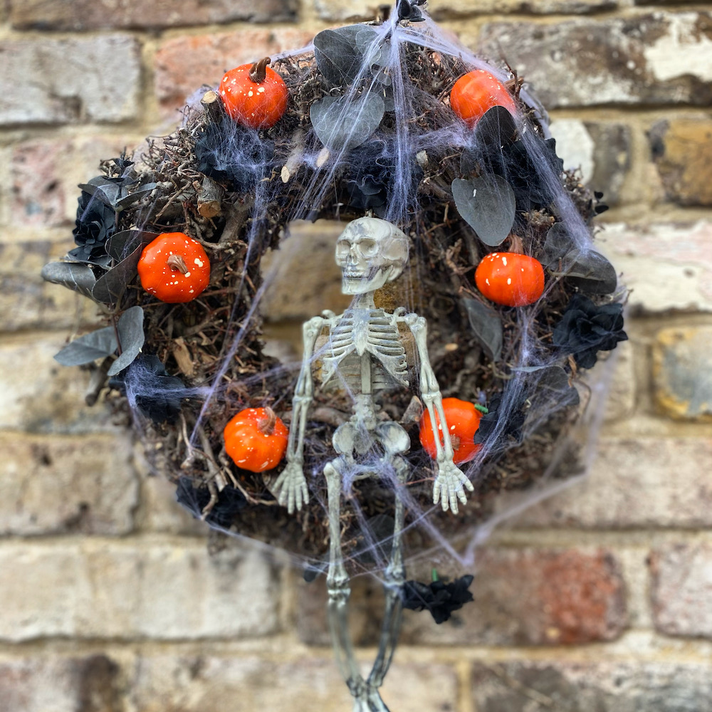 a twiggy Halloween wreath decorated with leaves, mini pumpkins and a skeleton from Woodland Wreath Company