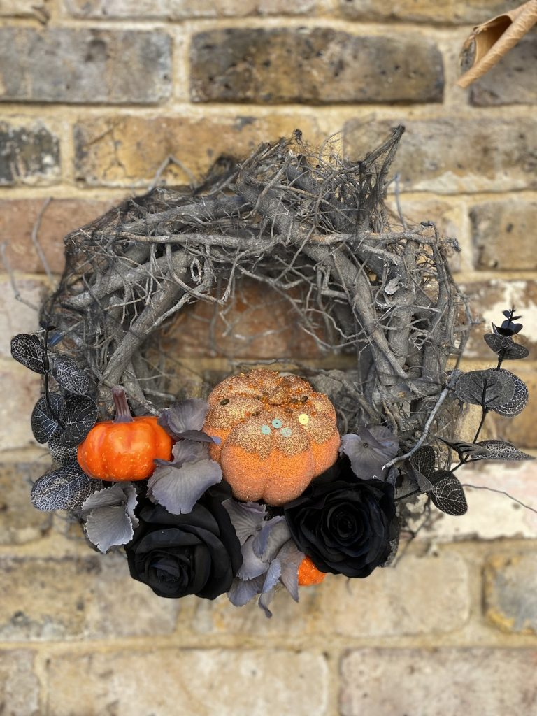a pumpkin halloween wreath made from twigs and decorated with pumpkins and black and grey flowers - wreath available from Woodland Wreath Company