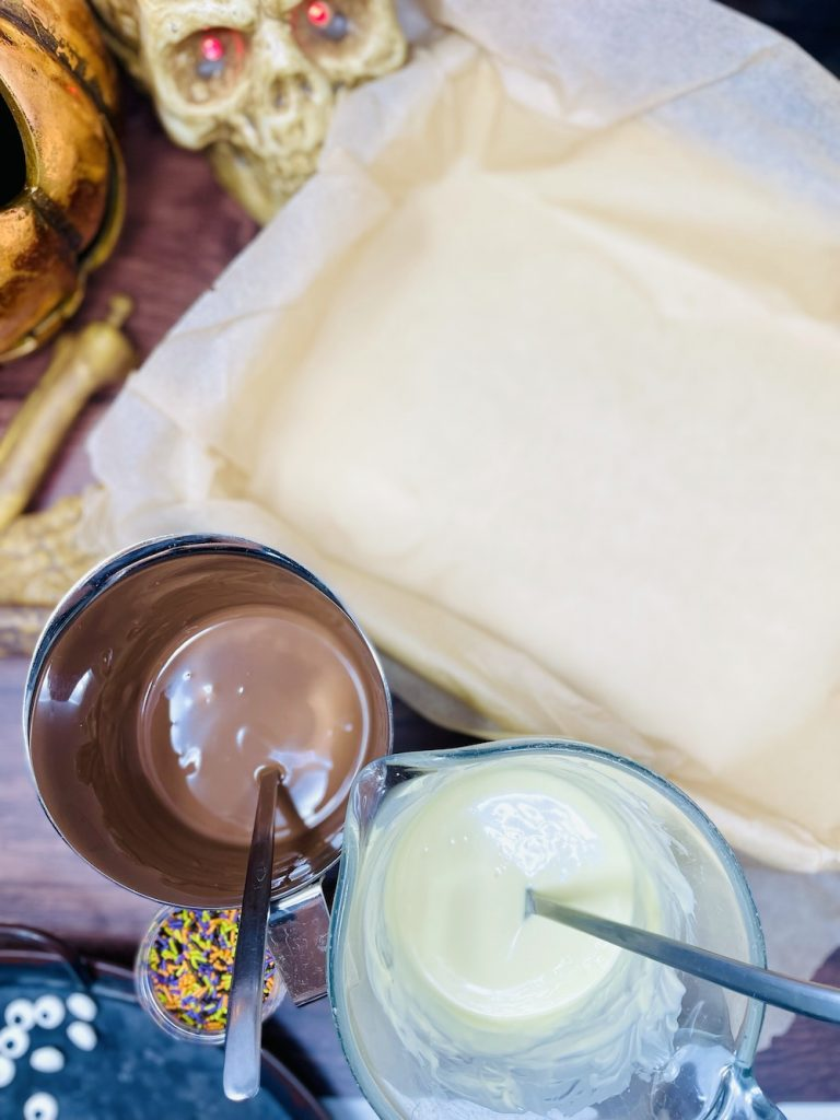 melted milk and white chocolate in jugs next to a tray lined with greaseproof paper