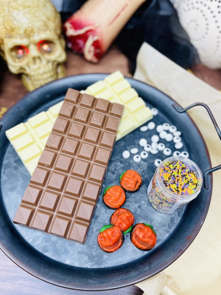 Halloween chocolate bark ingredients on a tray - milk chocolate, white chocolate, jelly pumpkins, edible eyes and Halloween sprinkles
