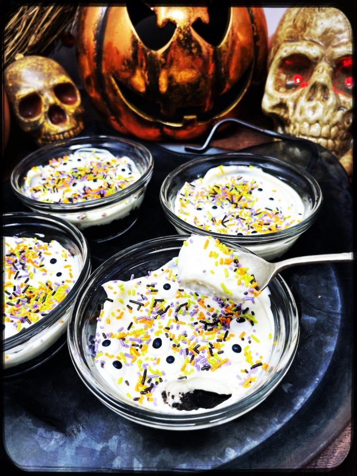 Halloween cheesecake with Oreo biscuit base topped with creamy vanilla frosting and decorated with edible eyes and Halloween sprinkles