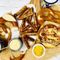 honey and mustard sausages served on a platter with pretzels, mustard mayonnaise, apple sauce and beer