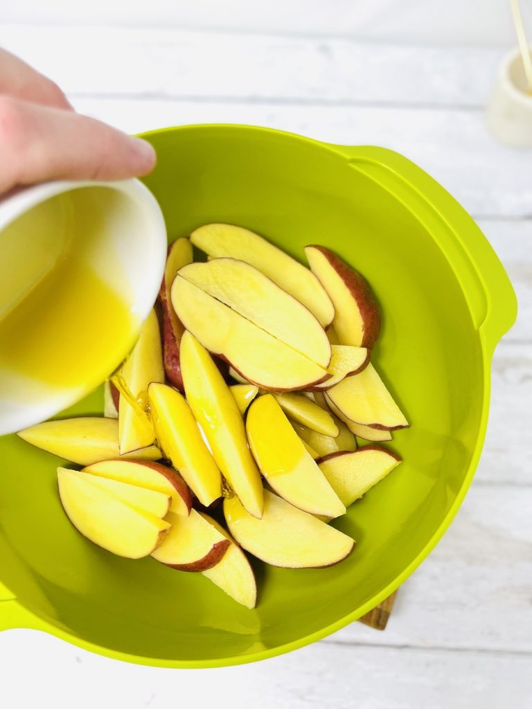 raw potato wedges being drizzle in olive oil