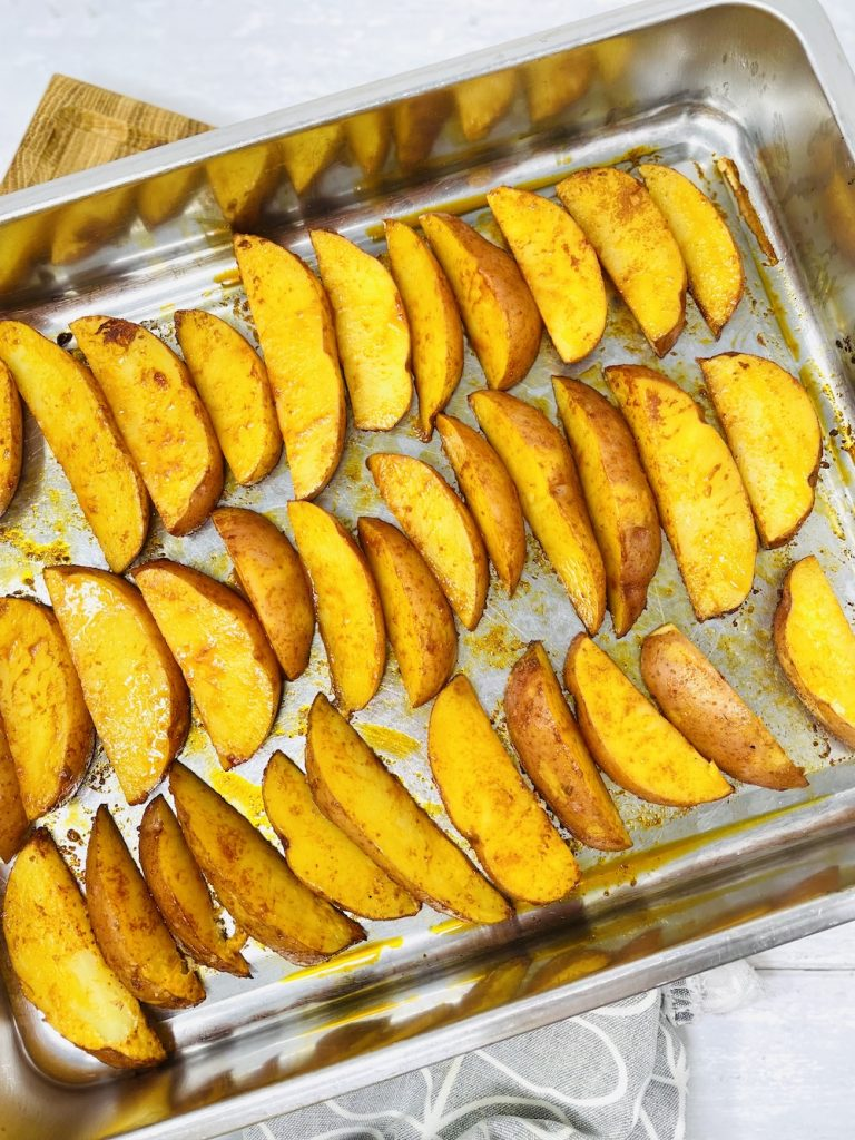 raw potato wedges being spread out on a baking tray ready to bake