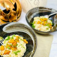 pumpkin risotto served in black bowls scattered with fresh herbs