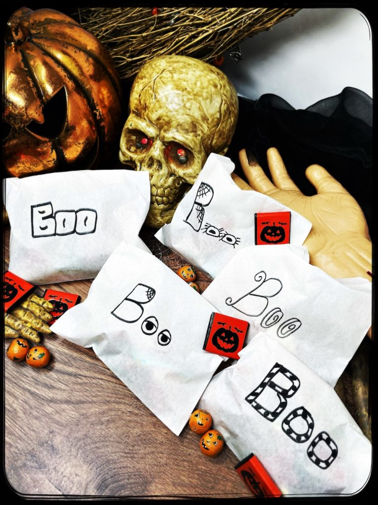 home-made trick or treat bags - white paper bags with boo written on them in spooky writing. Bags are filled with halloween sweets